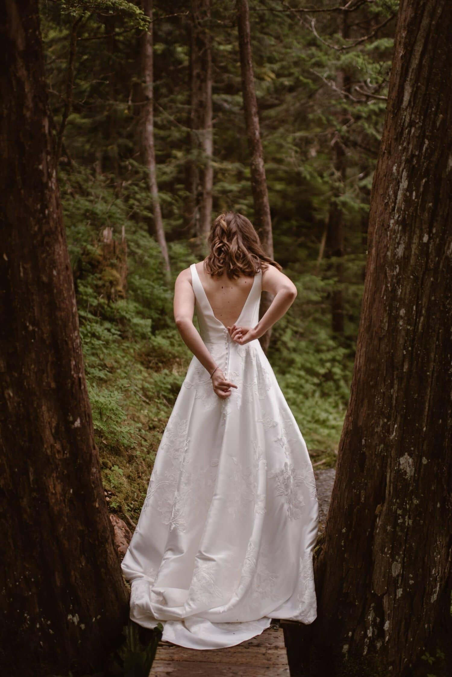 Bride zips up the back of her white wedding dress.