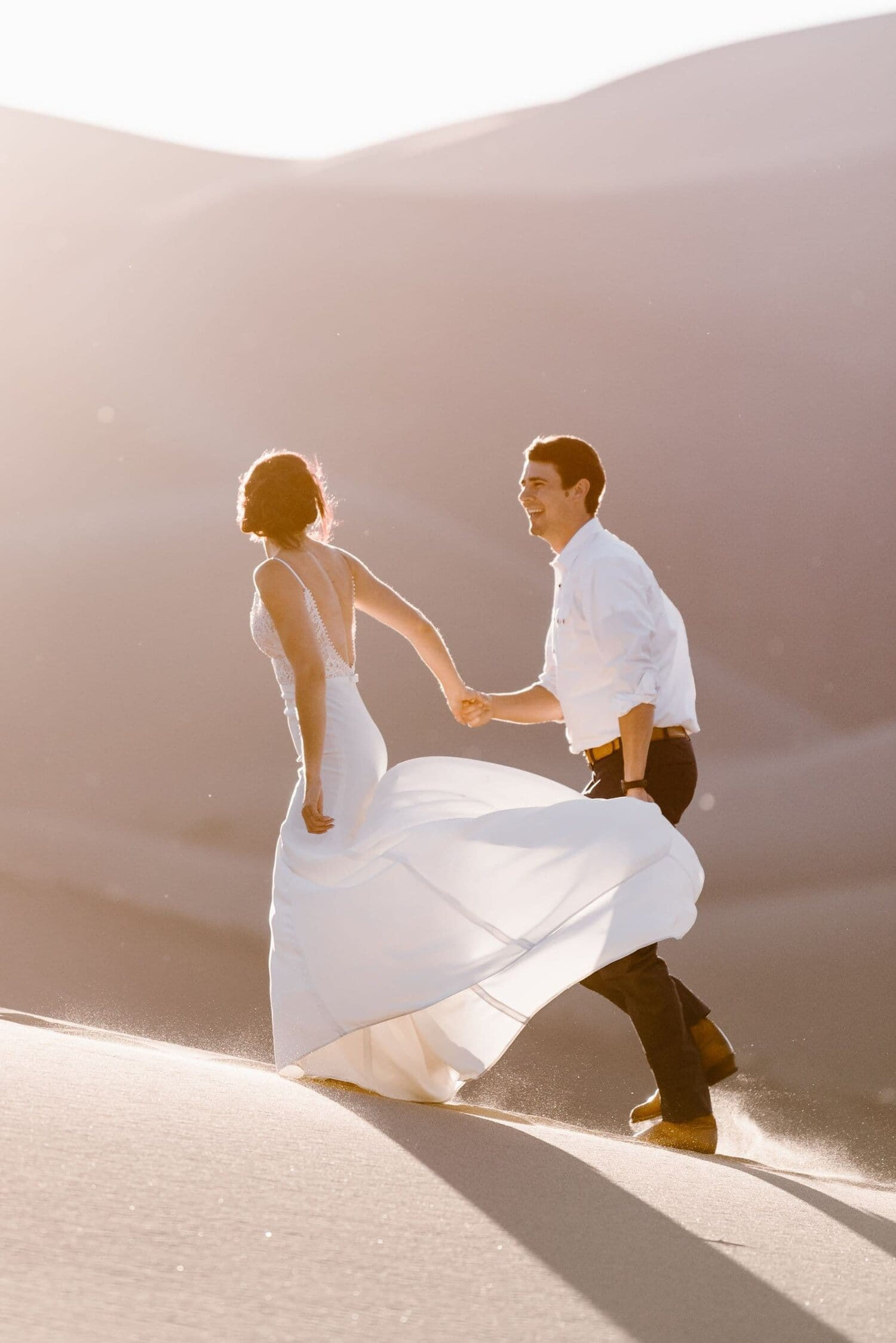 Bride and groom walk hand in hand on the sand dunes on their wedding day.
