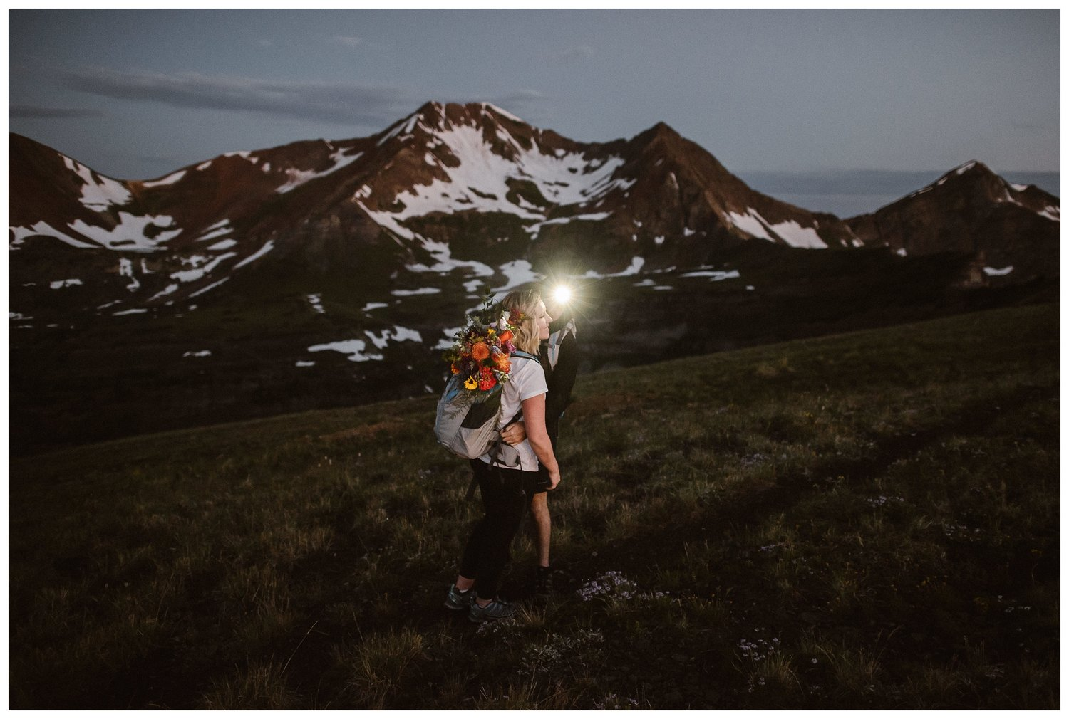 A couple wear headlamps as they hike up the mountains in the early morning.