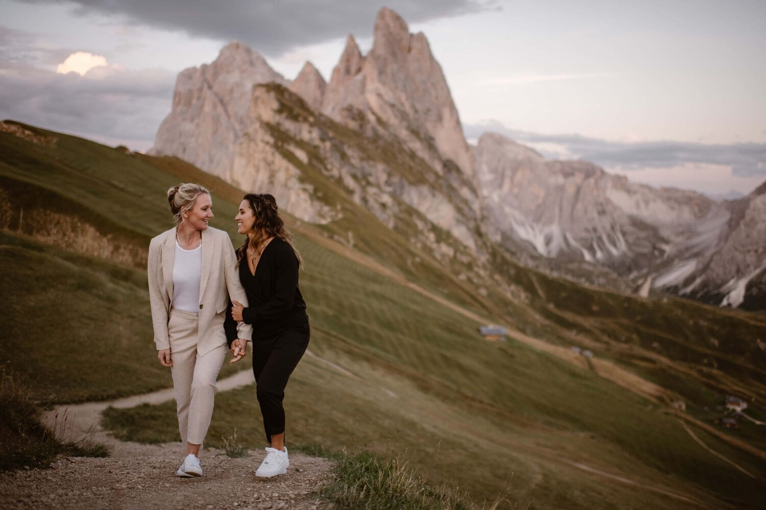 Two brides walk hand in hand in the Italian Dolomites.