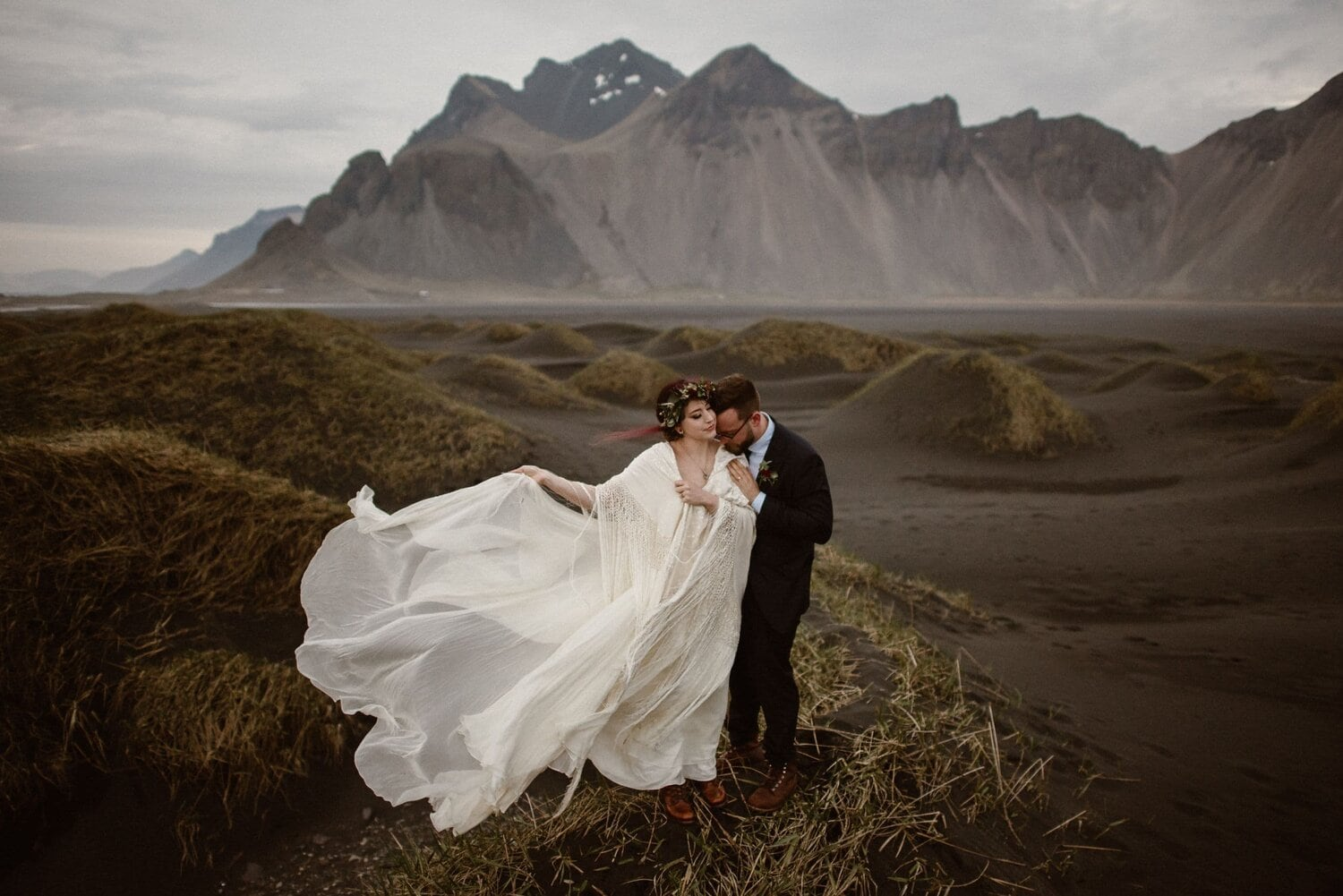 Bride holds her dress next to her husband in front of the mountains.