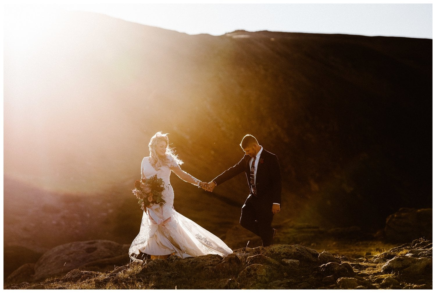 A bride and groom walk hand in hand during sunset.