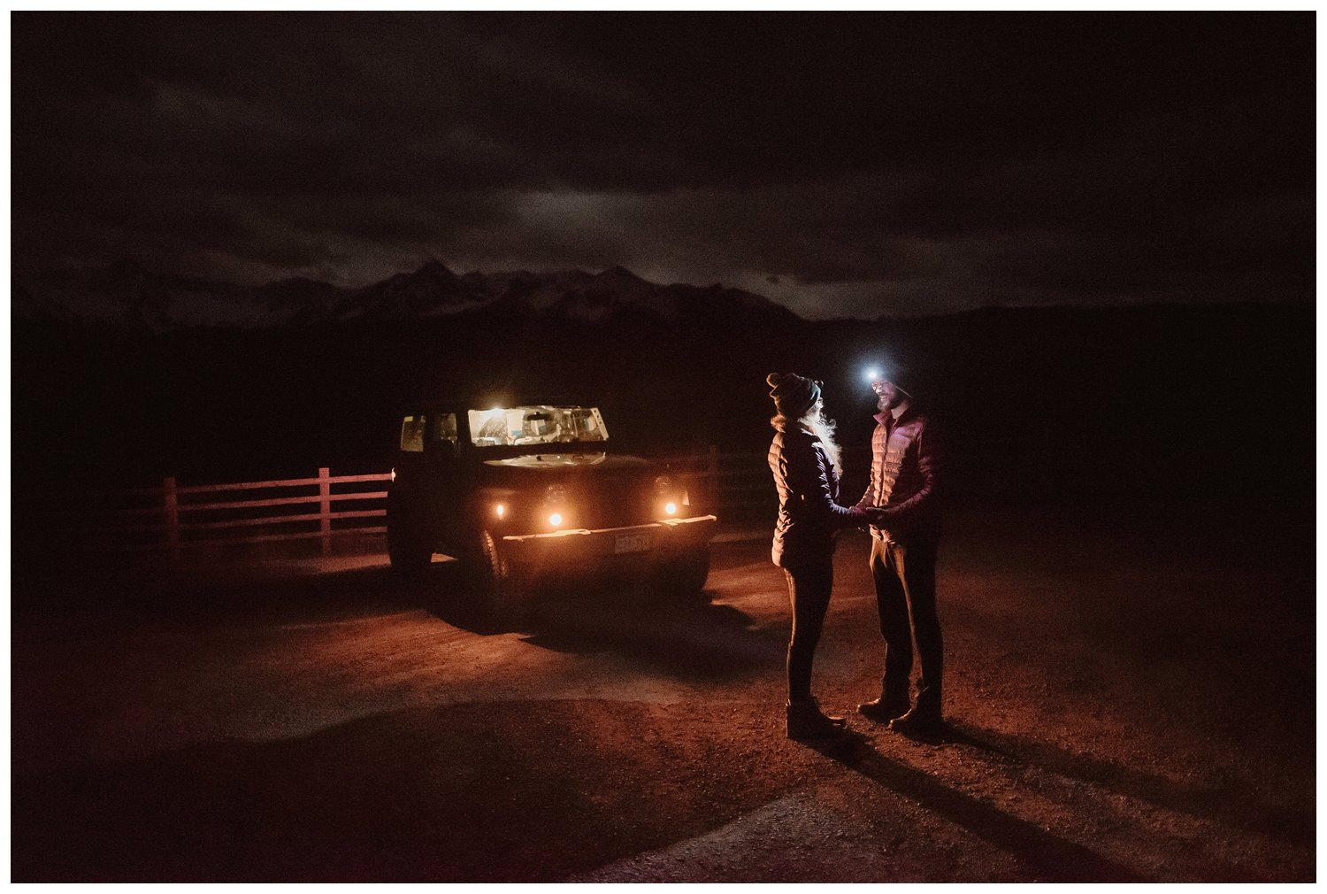 A couple hold hands in the dark with only headlamps and their jeep headlights for light.