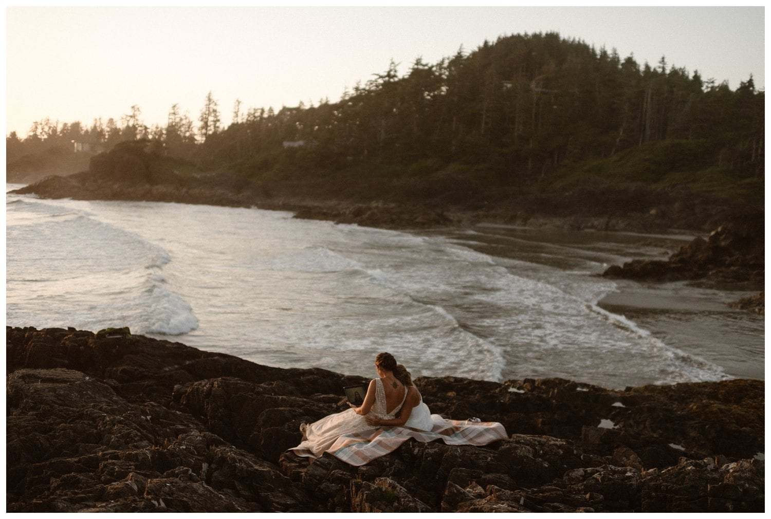 Two brides sit on the rocks by the beach during sunset.