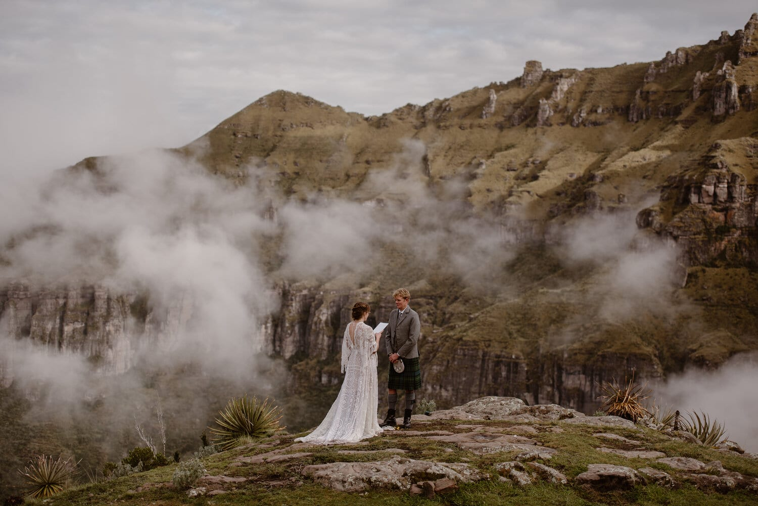 A bride and groom stand in the distance with the clouds and rocks of Peru in the background.