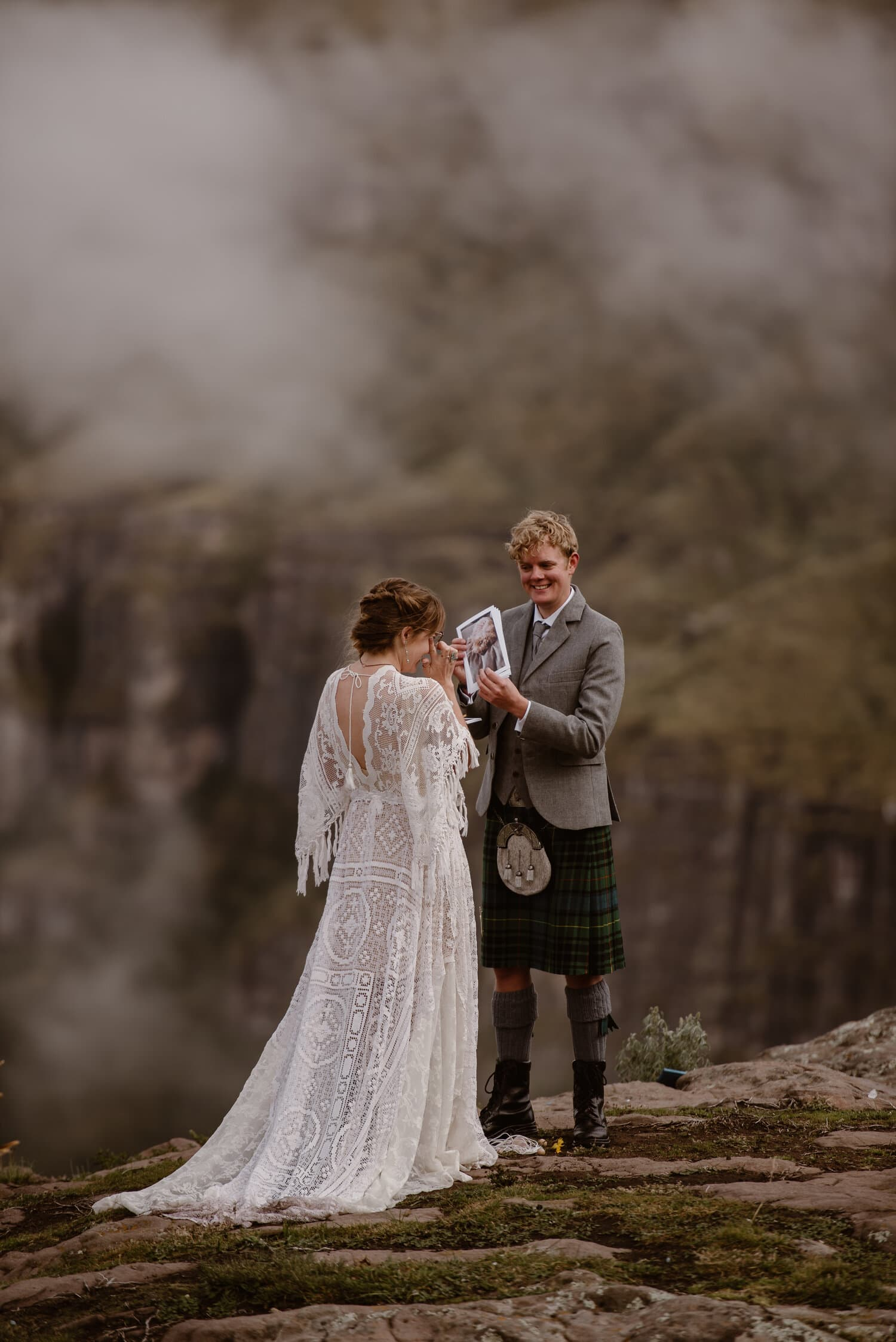 A groom, wearing traditional Scottish wedding attire, shares a photo with his bride as they exchange vows.