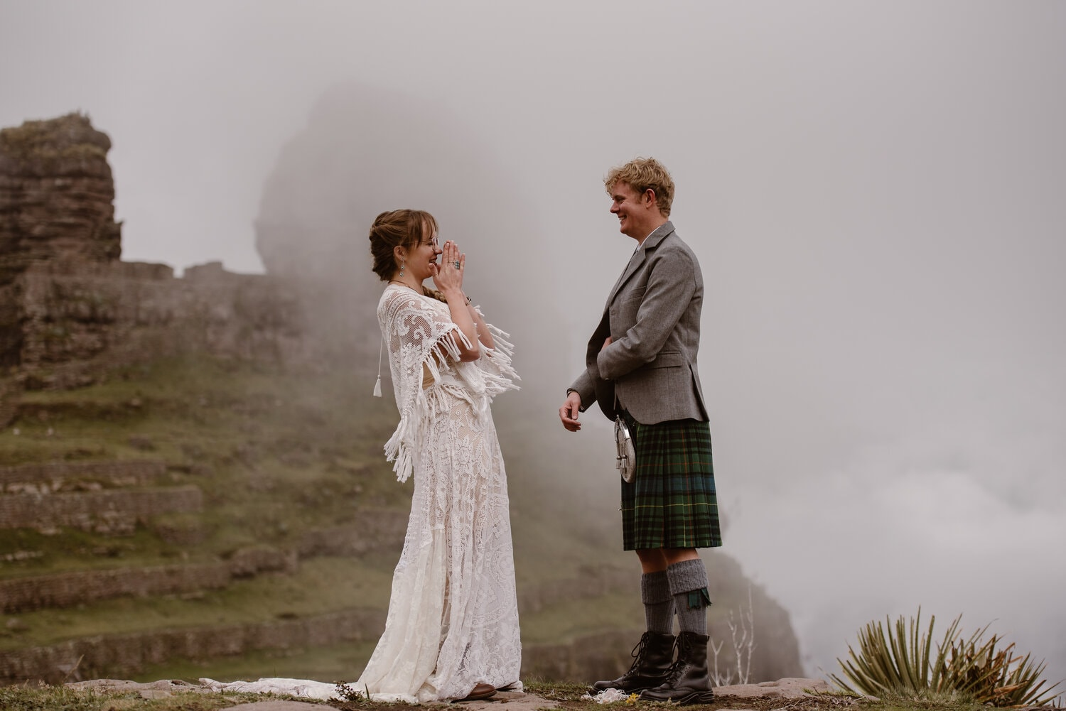 A bride in a lace wedding gown laughs as her Scottish husband looks on.