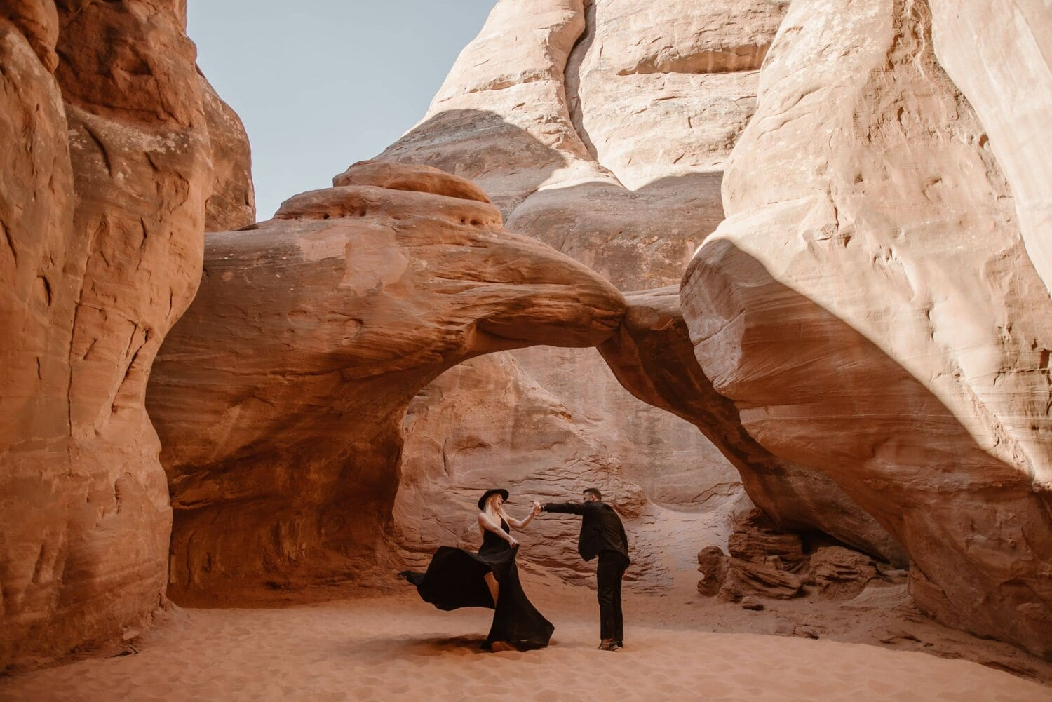 Bride and groom wear black in front of the orange arches on their wedding day.