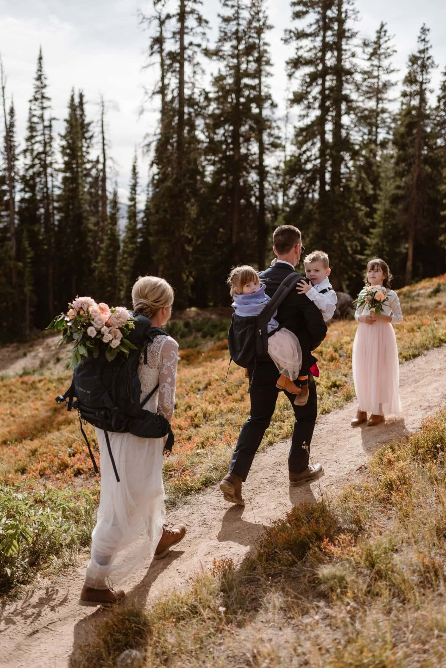 Bride and groom hike on a trail with their children on their elopement day.