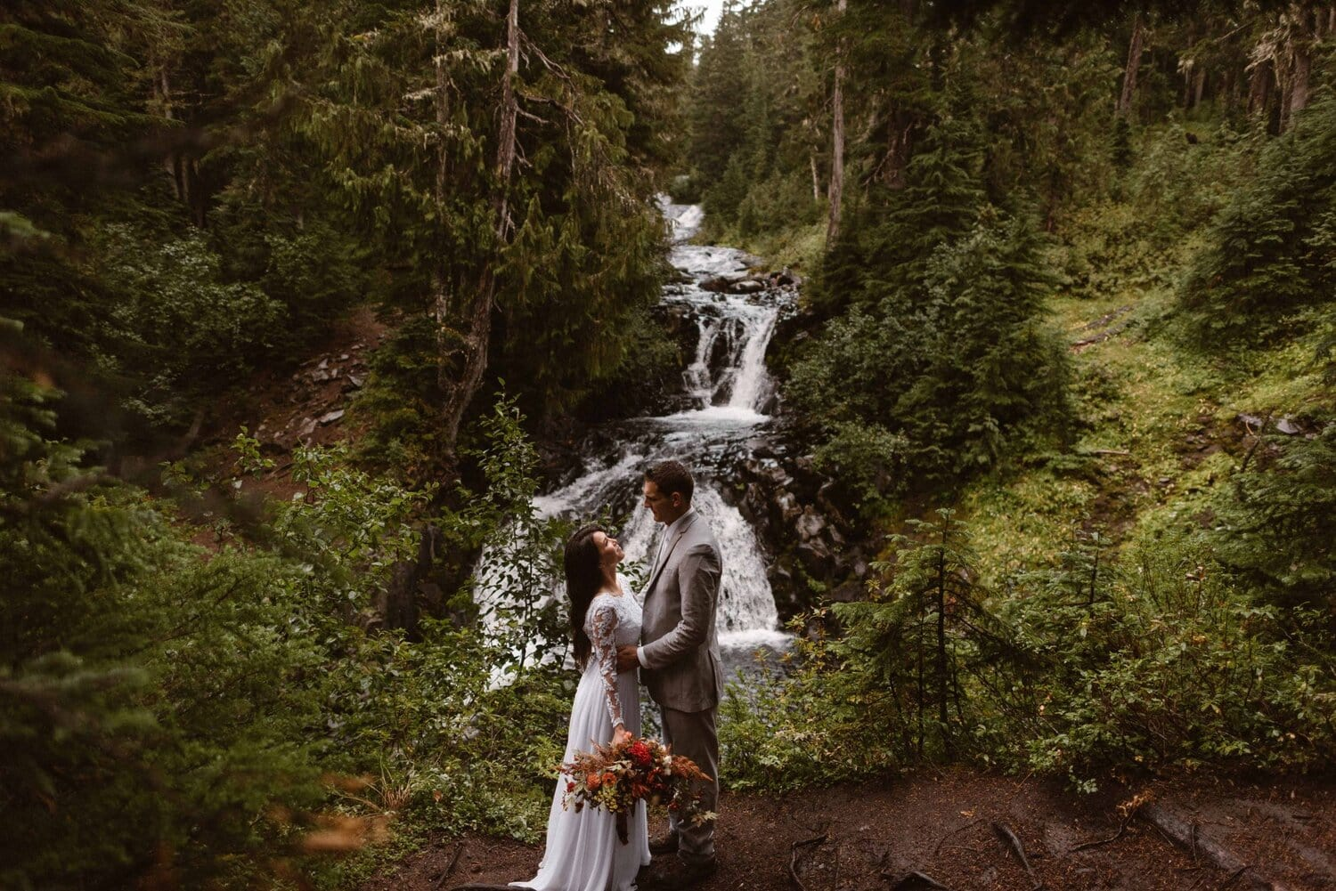 Bride and groom embrace near a waterfall during their wedding ceremony.