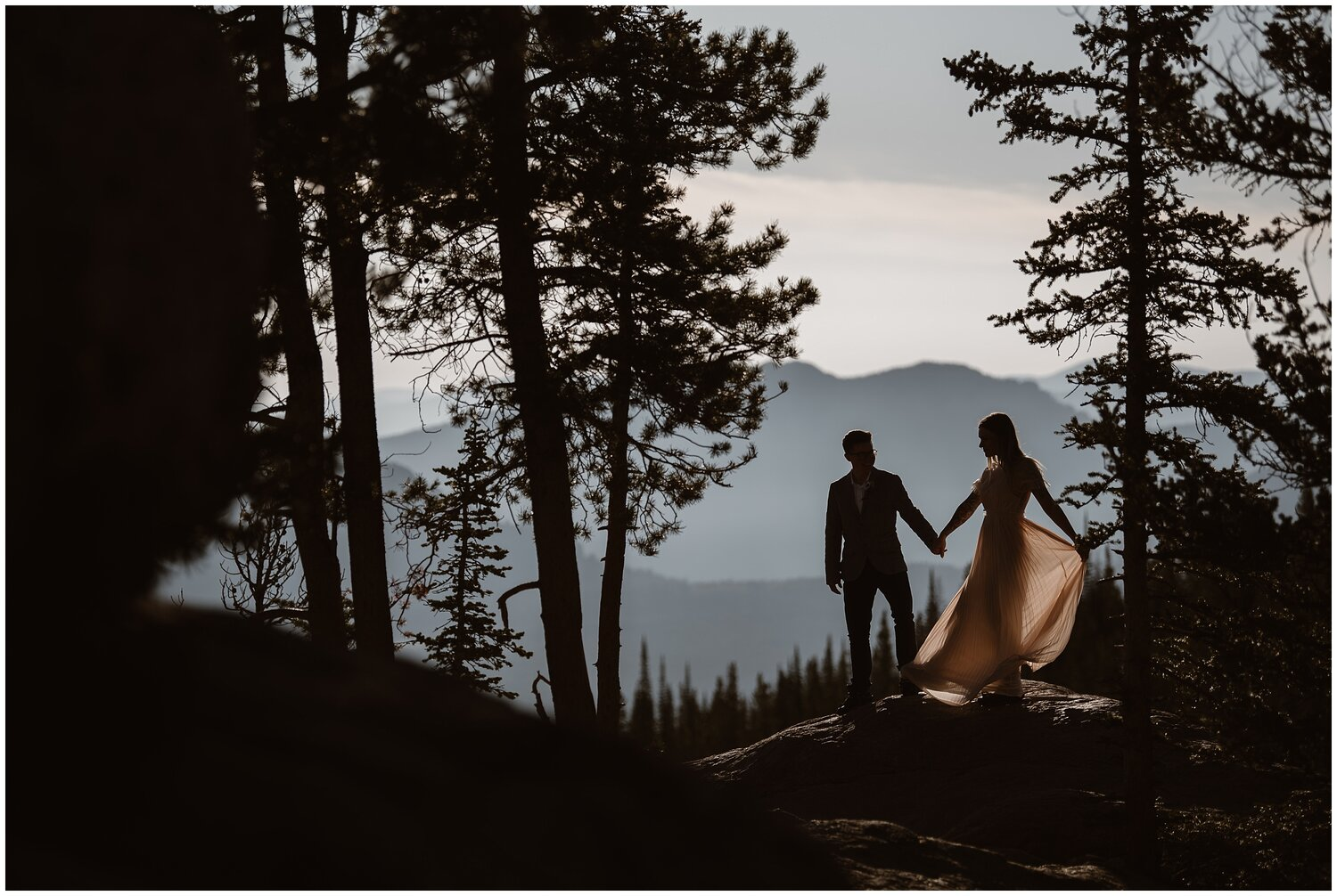 A bride and groom stand in the shadows of the forest on their wedding day.