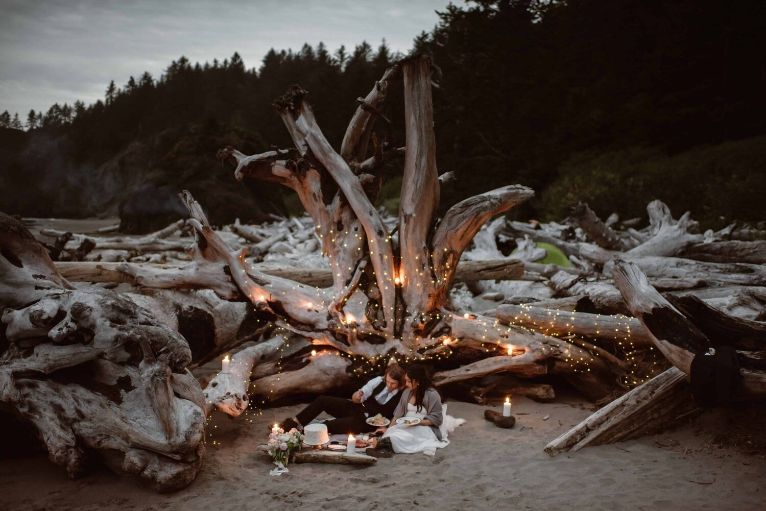 A bride and groom have a picnic at the beach during sunset.