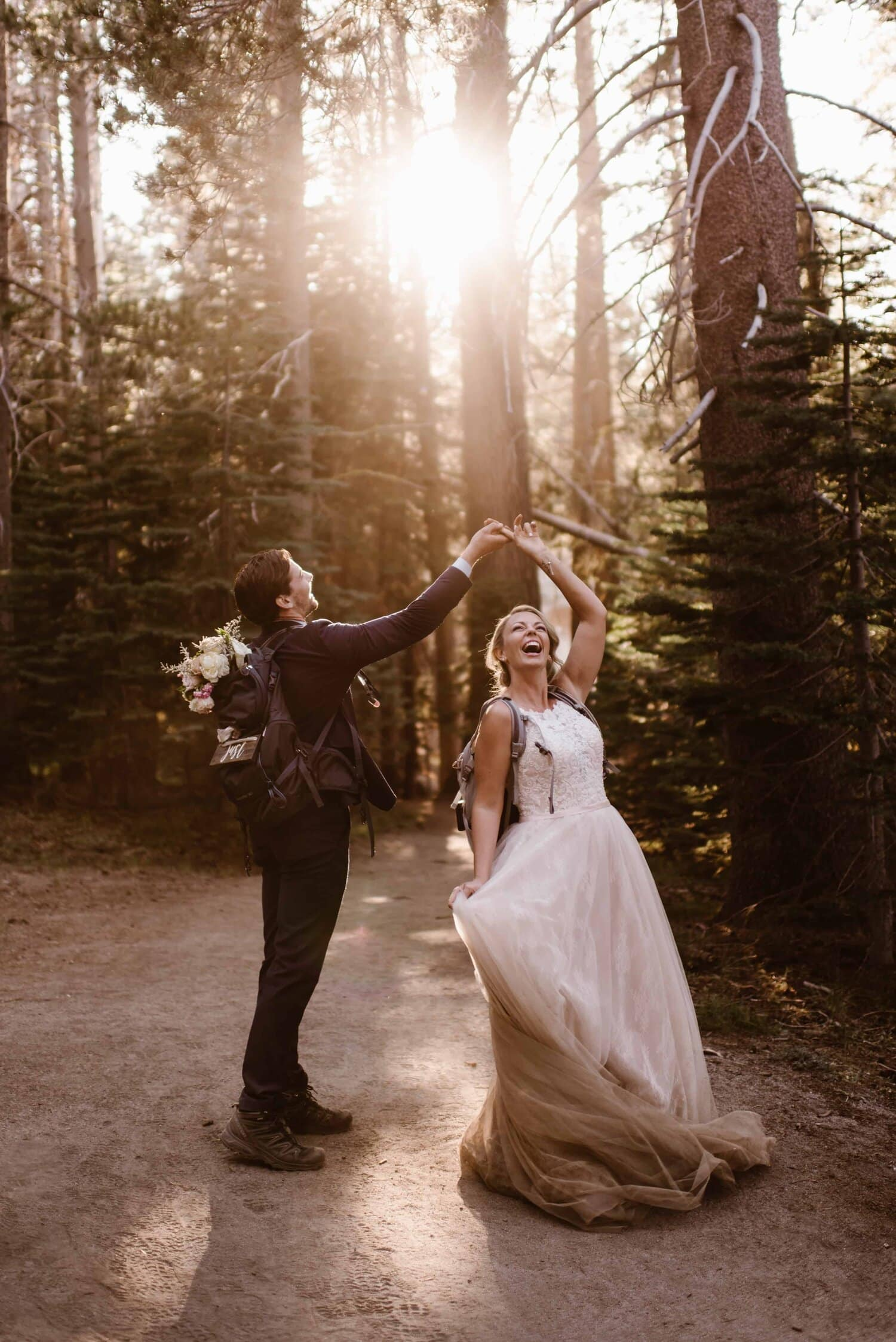A groom spins his bride in a forest while they both smile. They are both wearing backpacks.