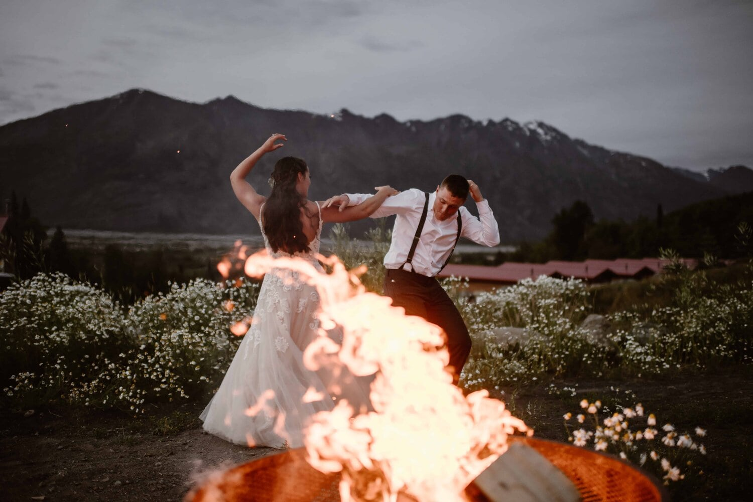A bride and groom dance in front of a fire while the sun is setting.
