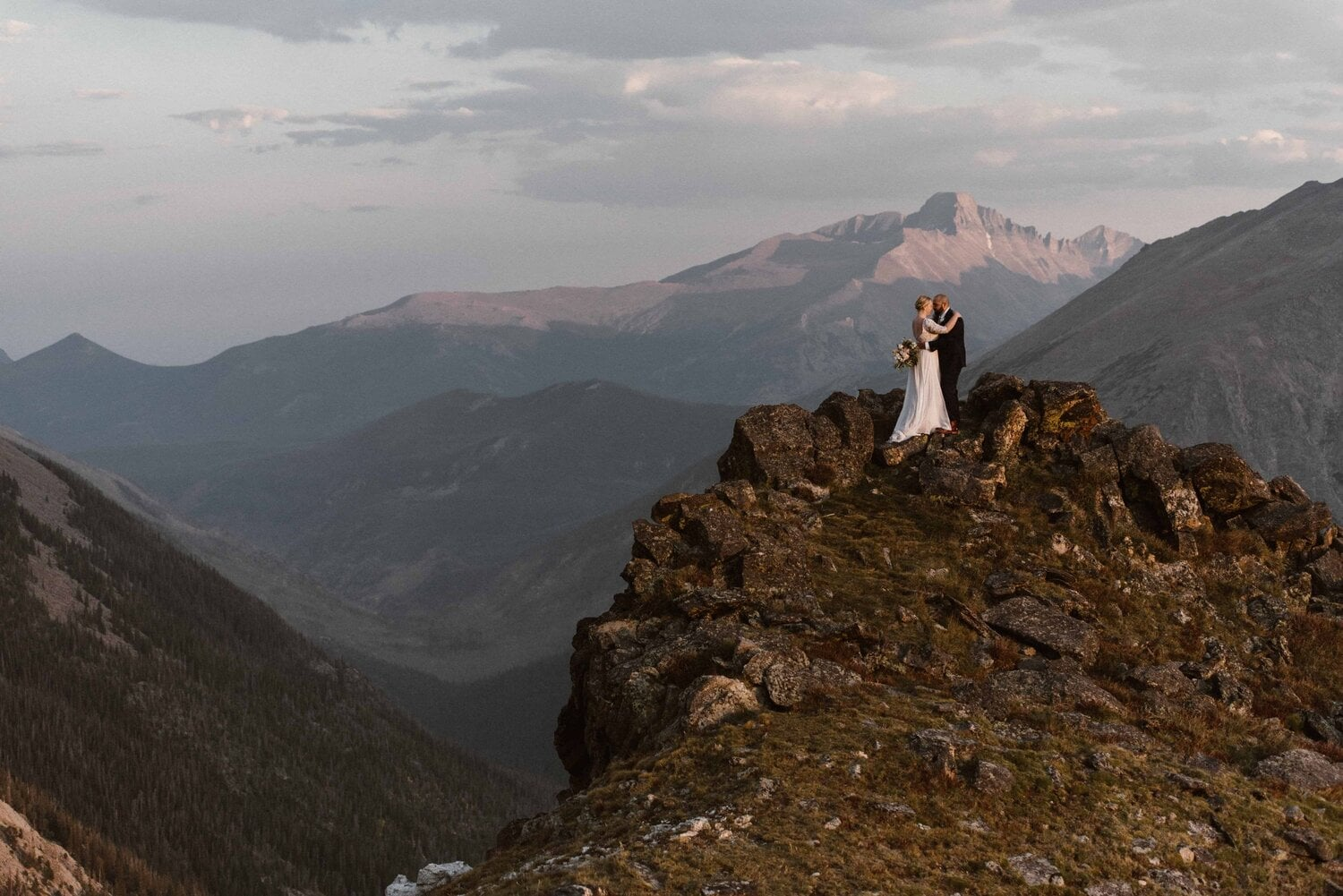 Bride and groom embrace on a mountain top.