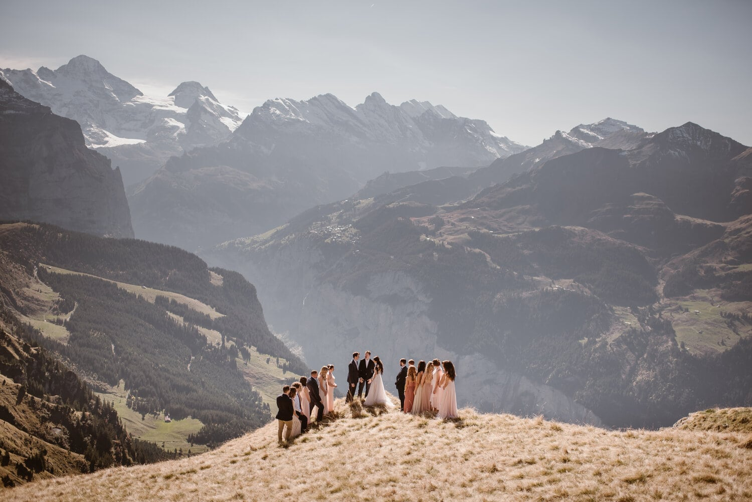 Intimate wedding ceremony on a grassy hillside in the mountains.