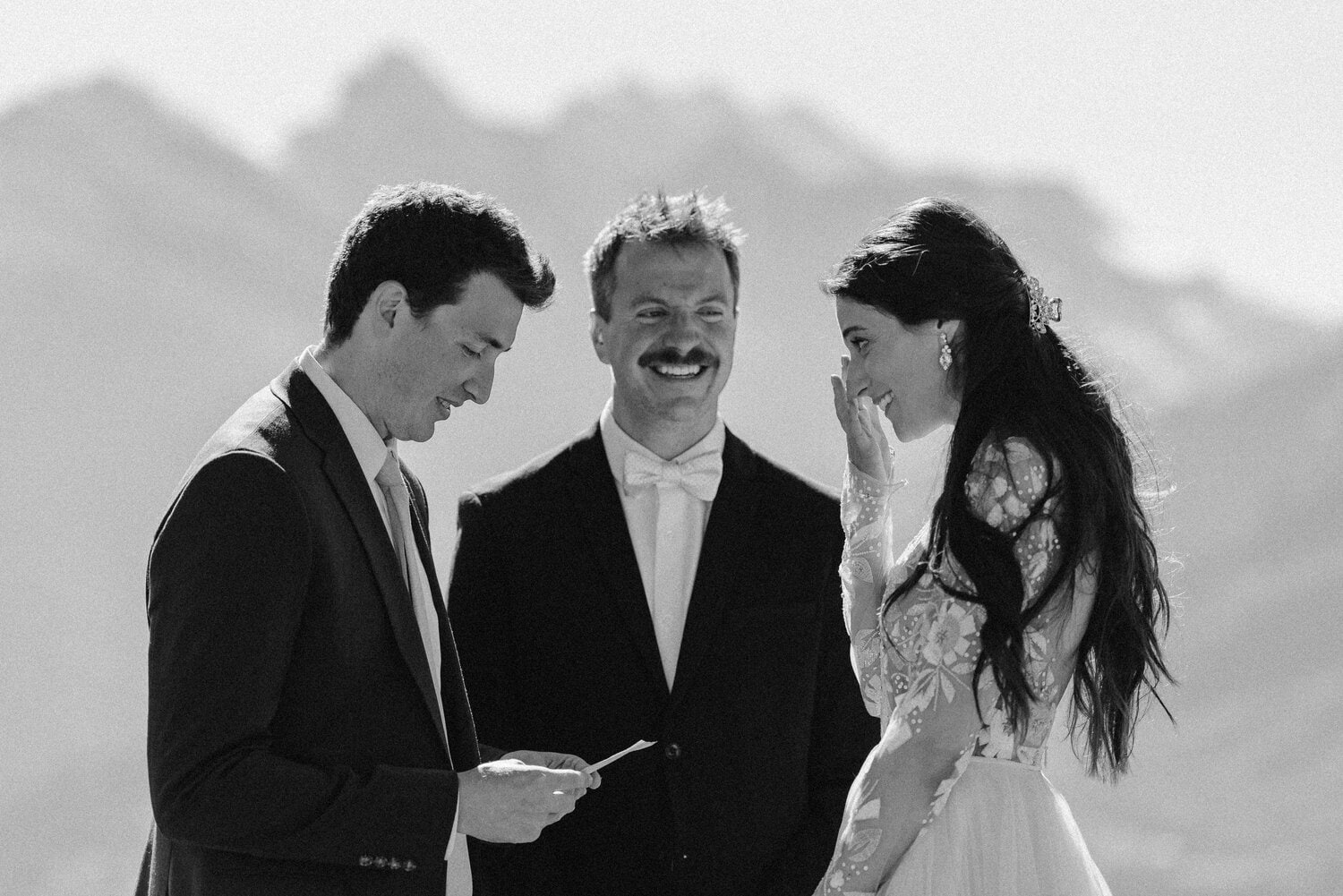 Groom reads personal vows to his bride while she looks on and cries. Photo in black and white.