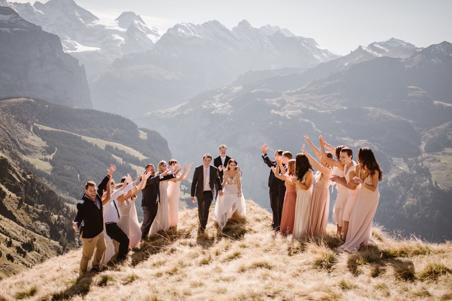 Intimate wedding bridal party cheer while newlyweds walk down the aisle during their mountain elopement.