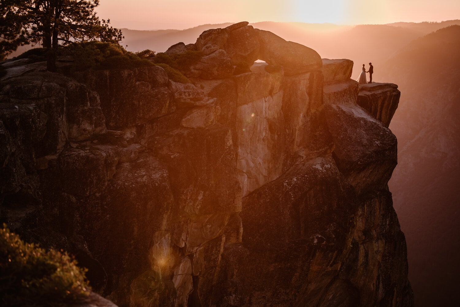 Bride and groom holds hands at sunset at Yosemite National Park.