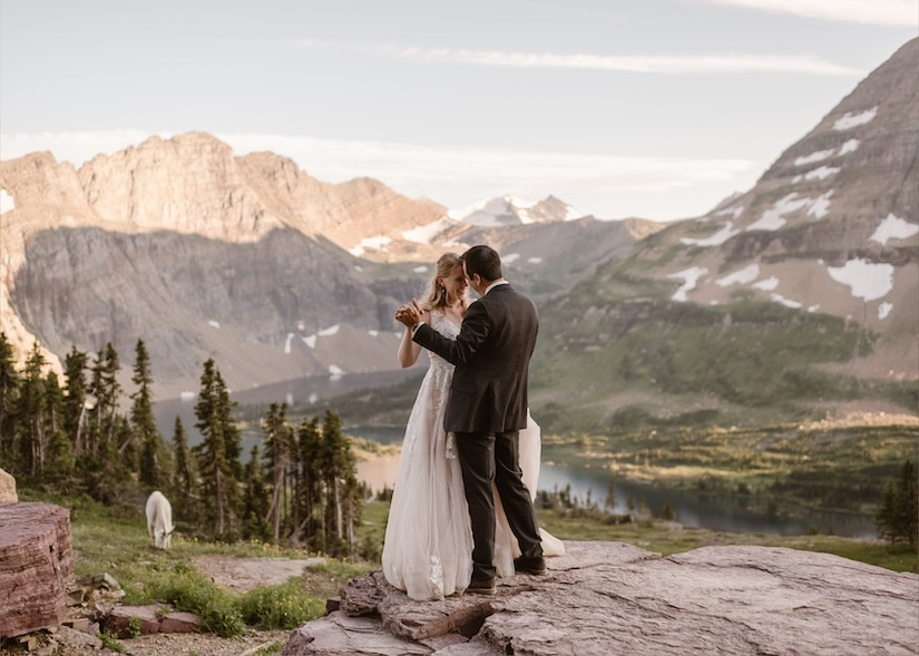 Bride and groom embrace and hold hands in the mountains.