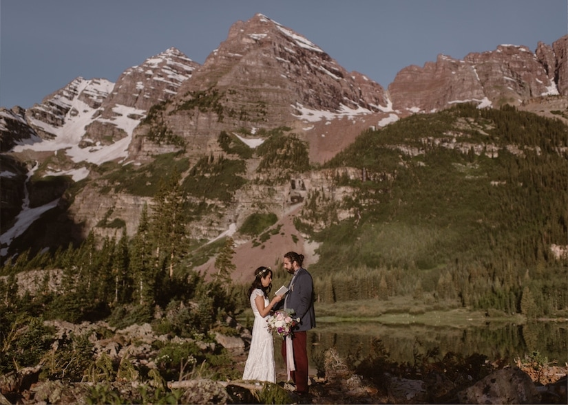 Bride and groom read vows in the mountains during their wedding ceremony.