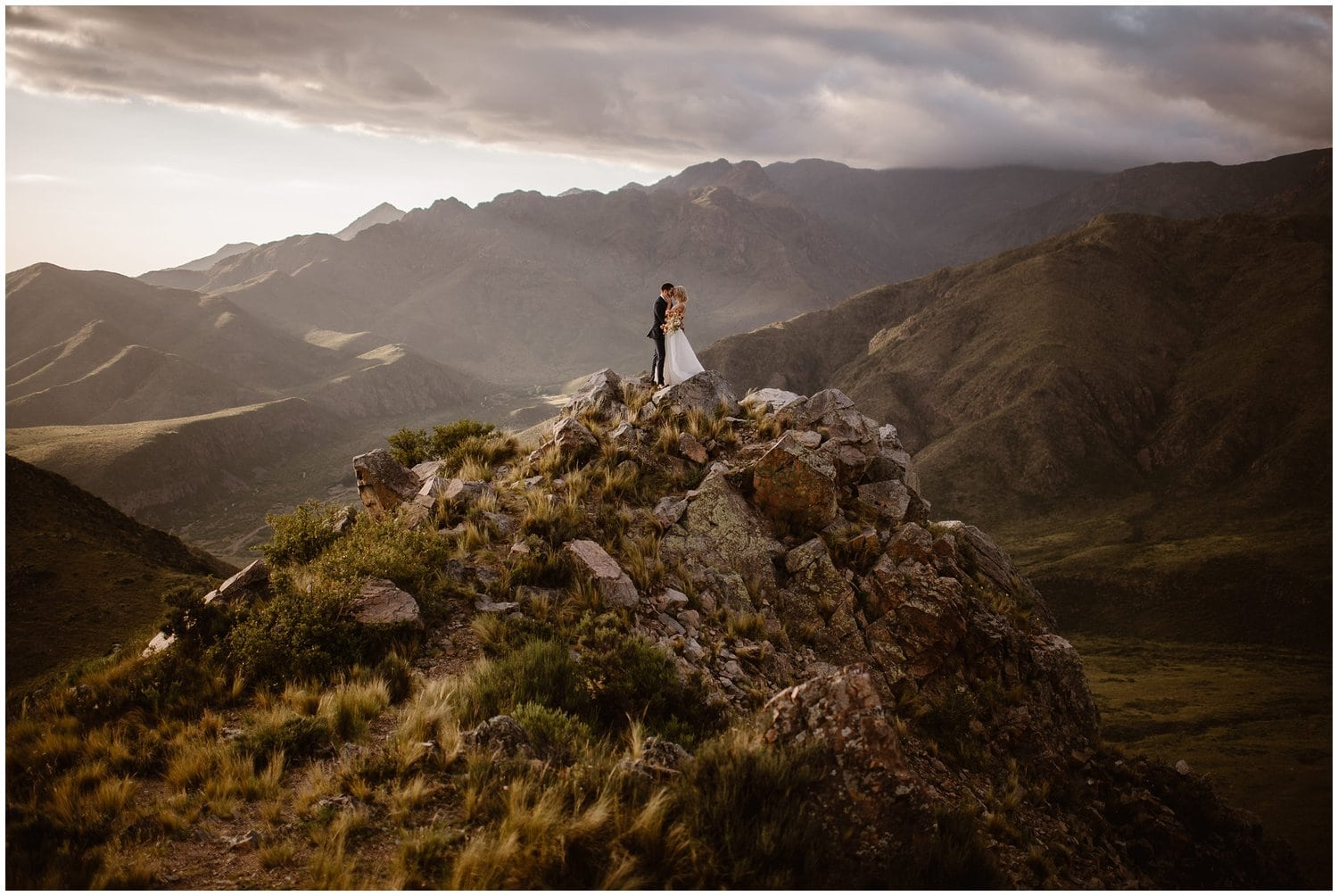 Bride and groom embrace on a mountain on their wedding day,