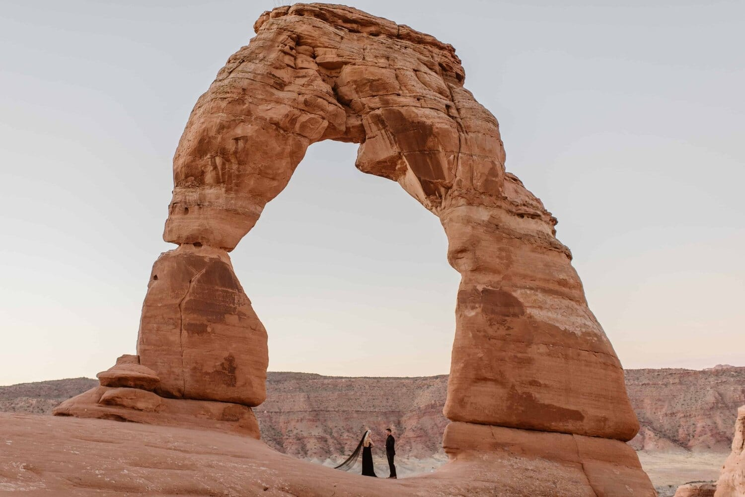 Bride and groom wear black wedding attire while standing underneath an arch for their wedding ceremony.