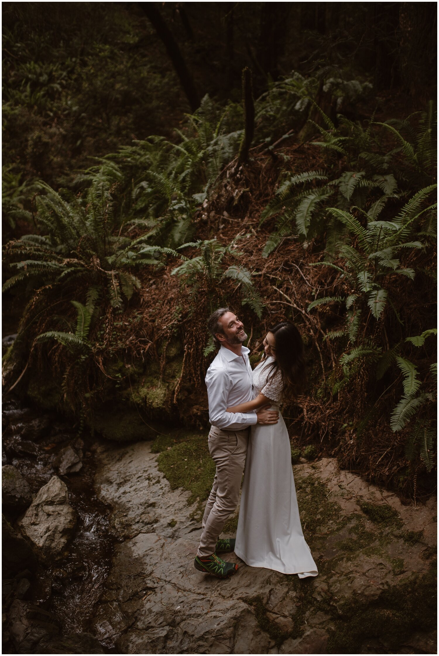Bride and groom smile at each other in the forest on their wedding day.