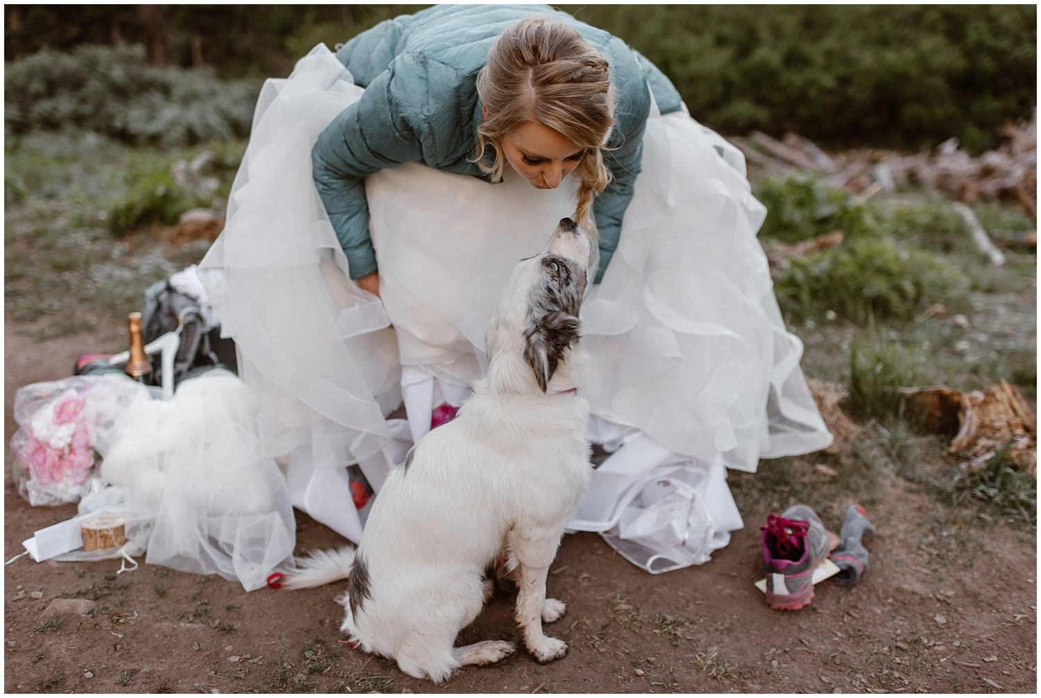 A bride bends down to kiss her white dog on her wedding day.
