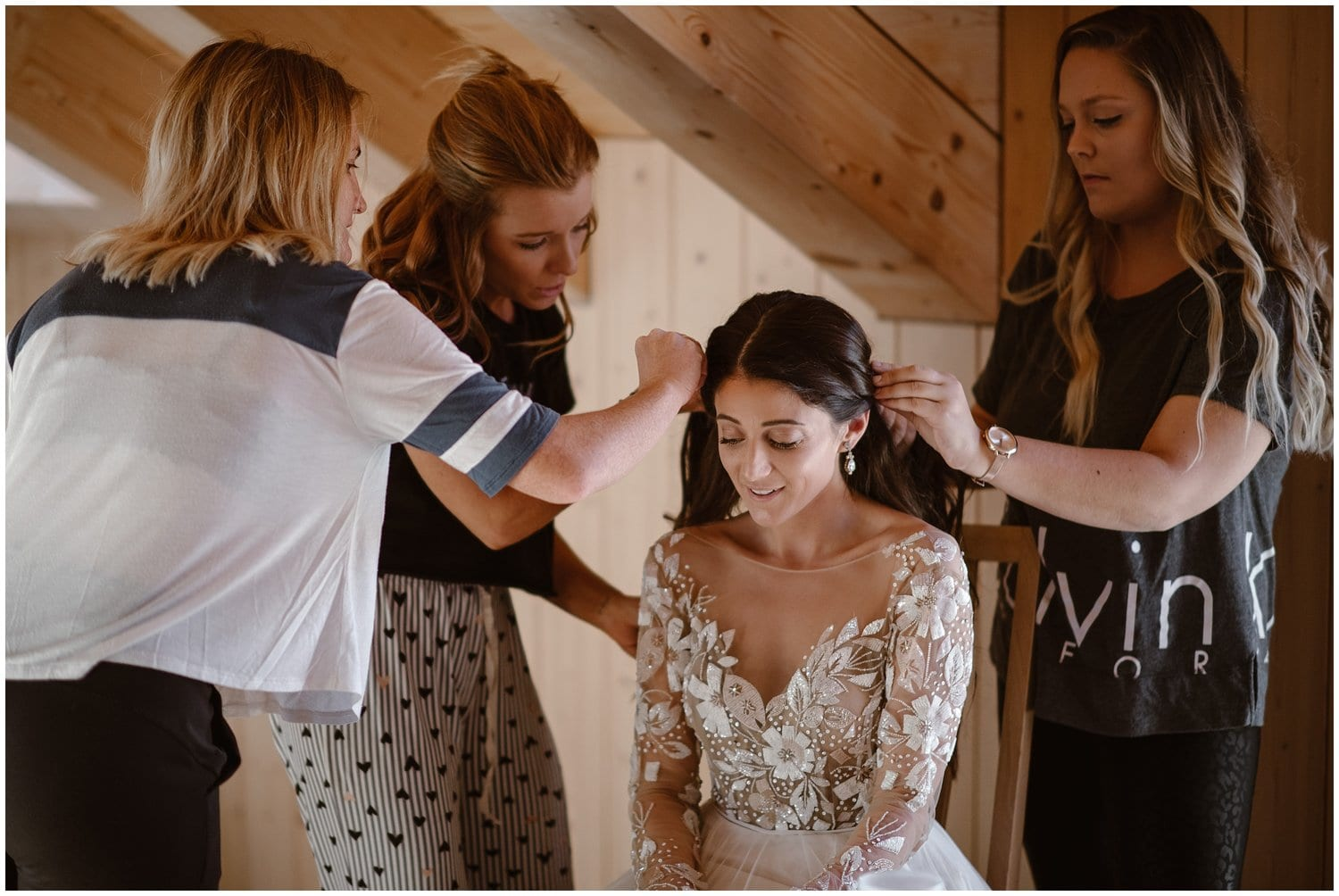 A bride sits in a chair while three women help with pin up her hair.