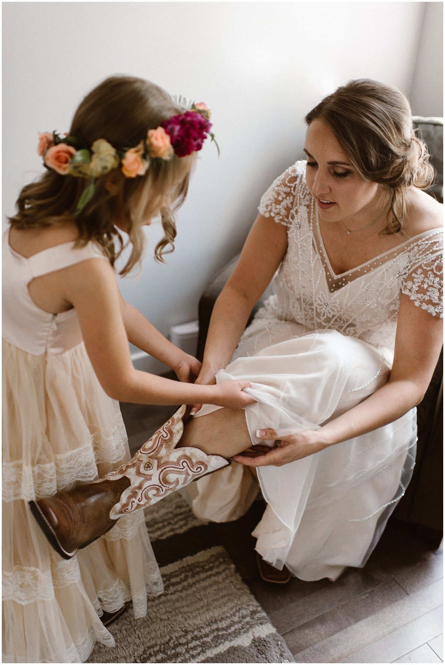 Little girl in a flower crown helps a bride put boots on for her wedding day.