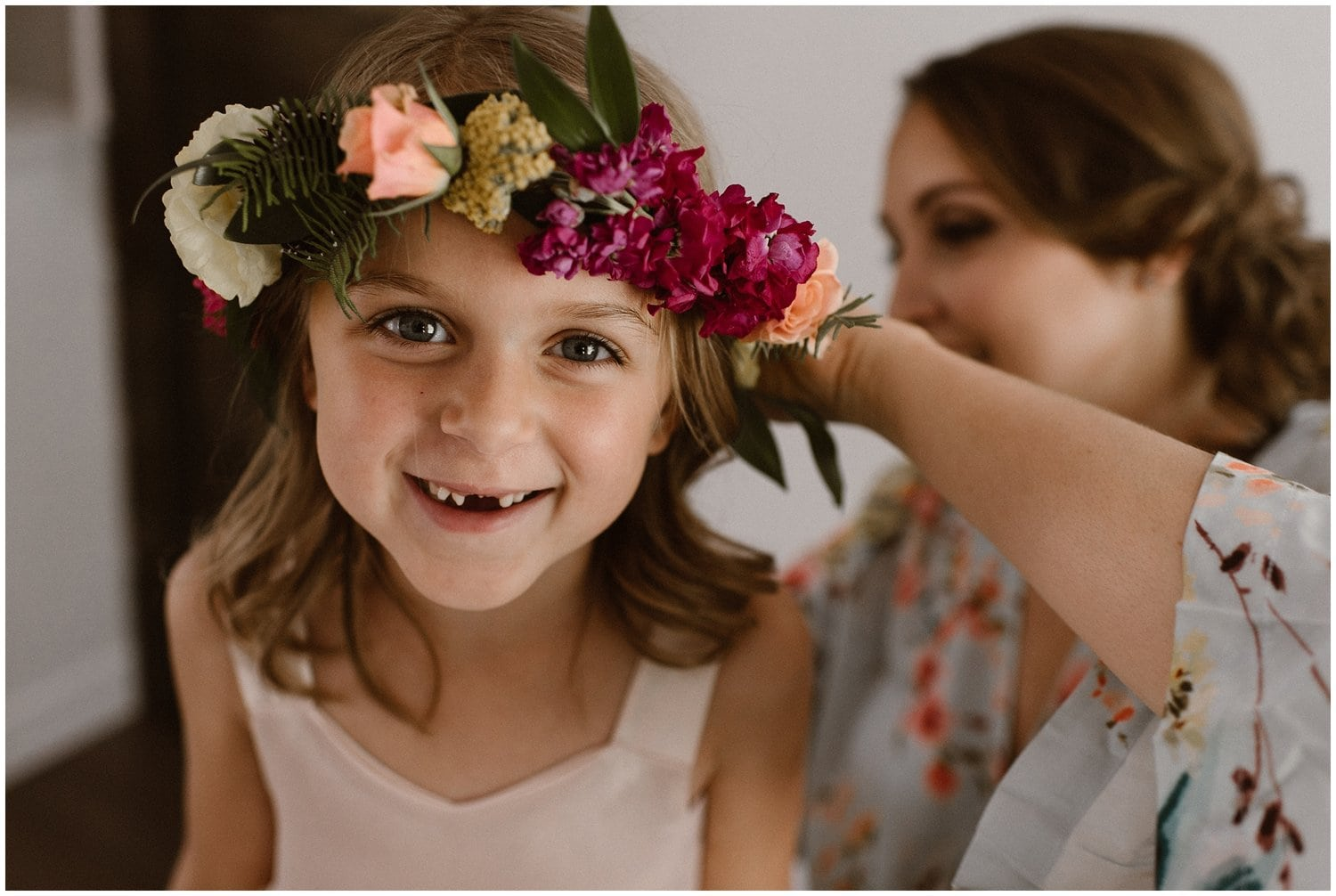 Little girl wearing a flower crown smiles at the camera.
