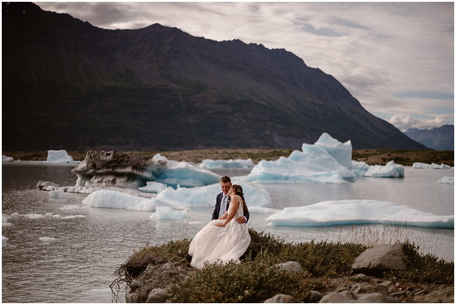 Bride leans on groom during their elopement in front of icebergs and mountains.