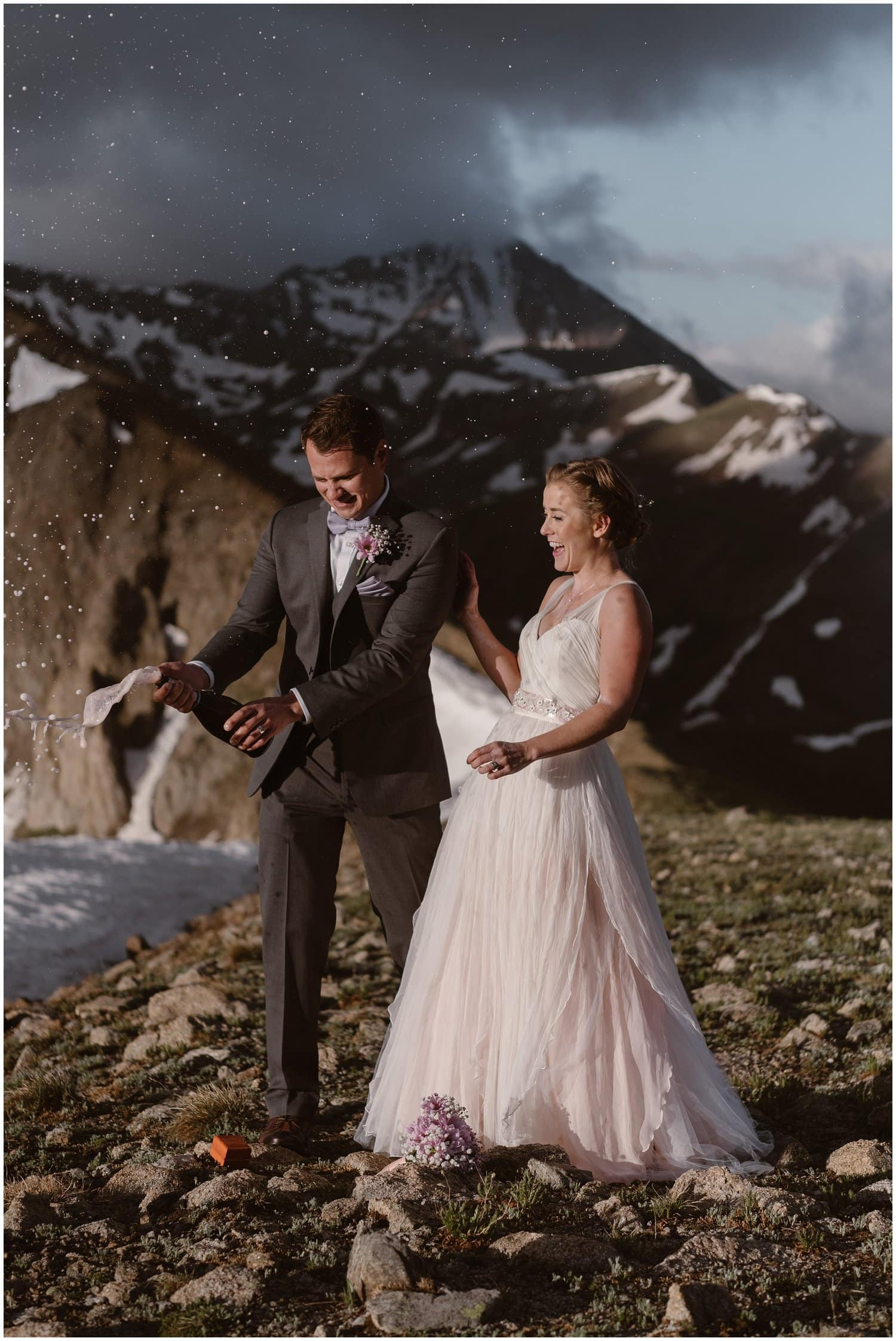 A bride and groom pop a bottle of champagne in the snowy mountains on their wedding day.