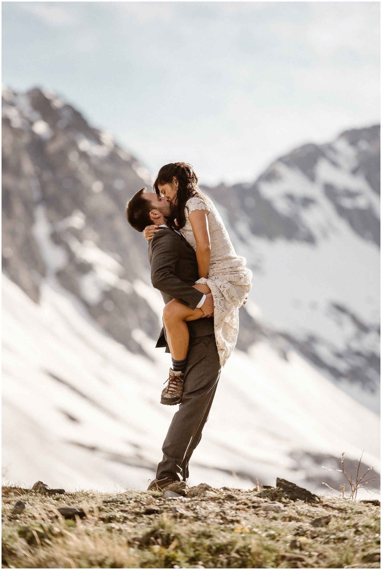 Groom picks up bride as they kiss in the mountains on their wedding day.
