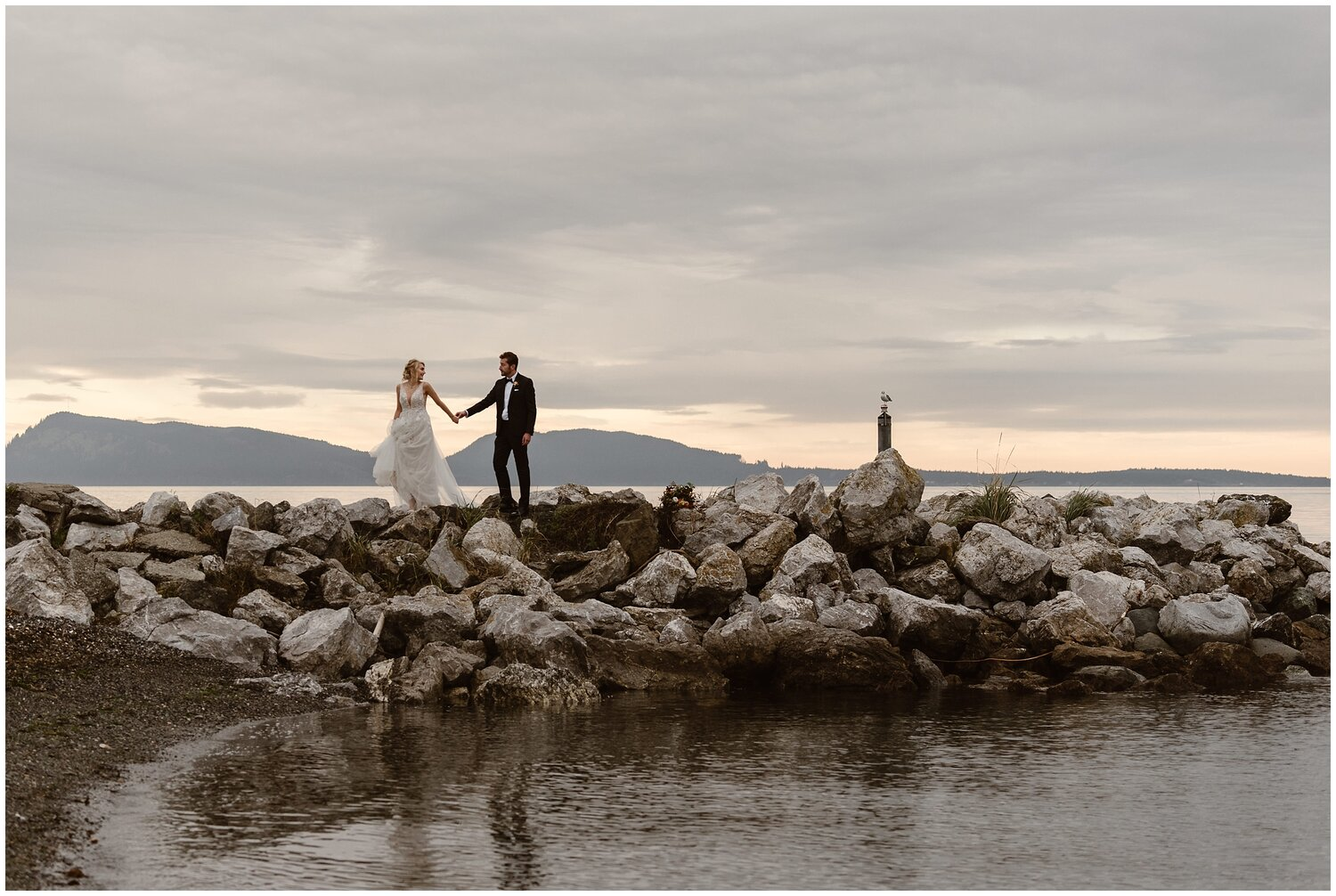 Bride and groom walk along the water on their wedding day.