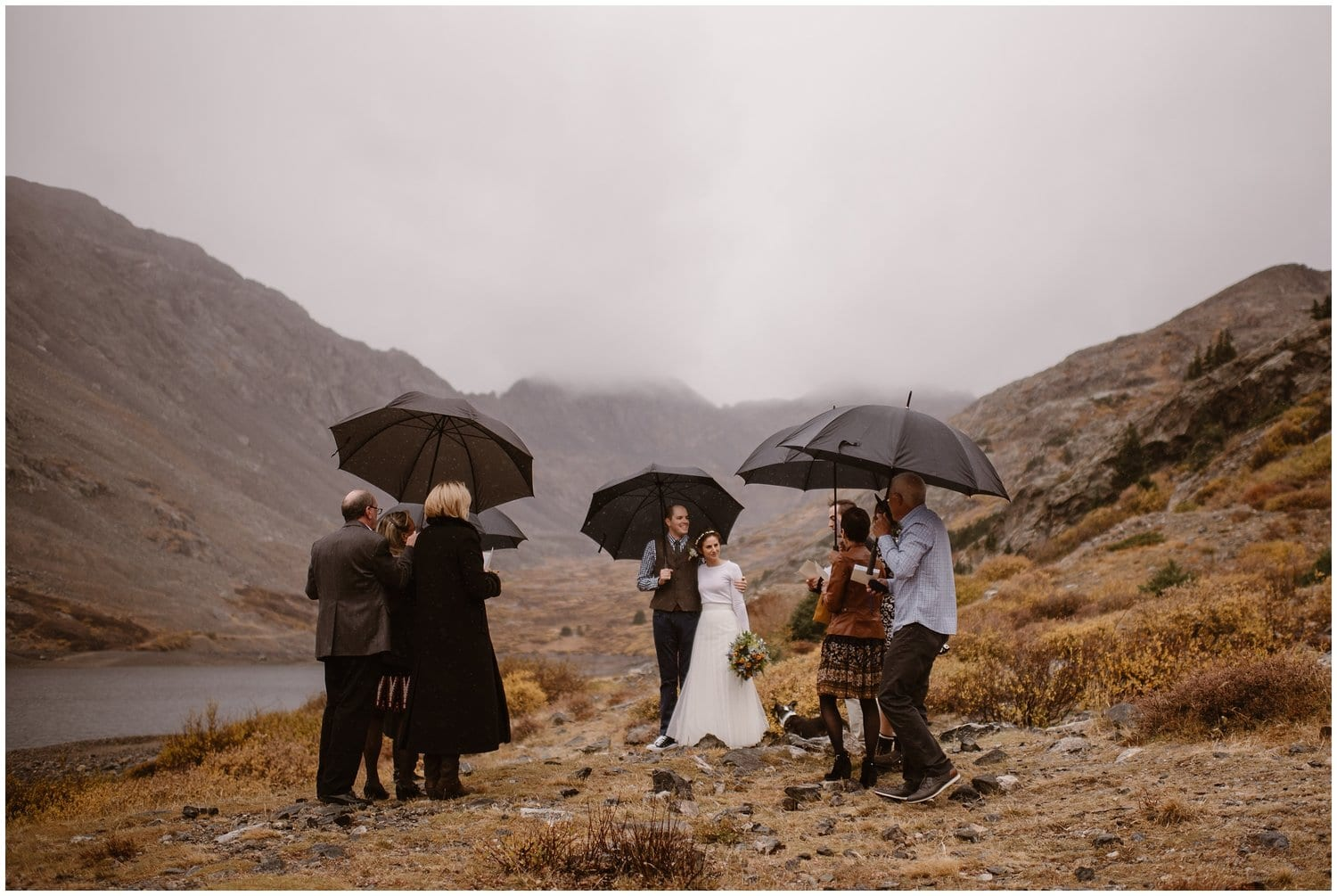 A bride and groom look at their loved ones while holding umbrellas during their wedding ceremony.