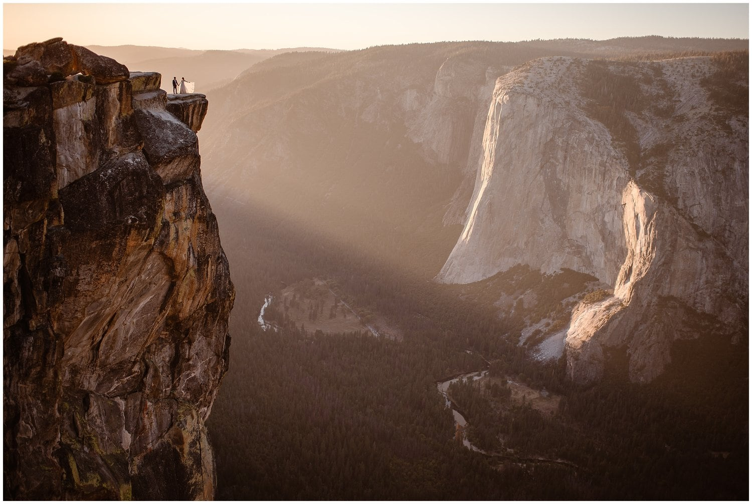 A couple stand at the edge of a cliff on their wedding day.
