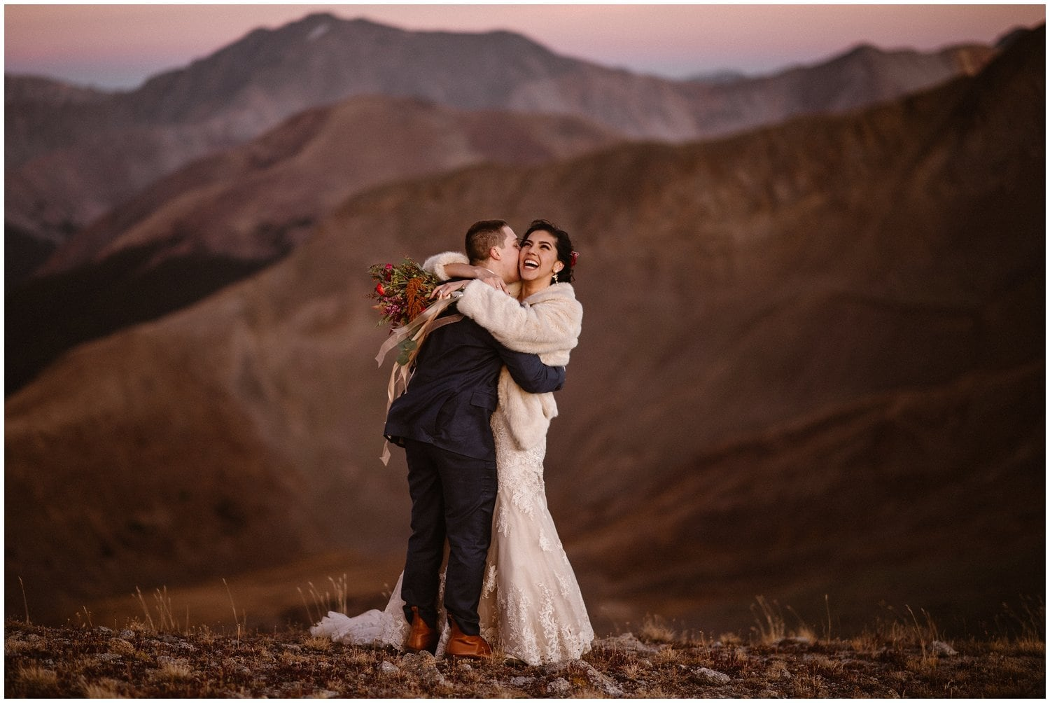 A bride and groom embrace on a mountain top on their elopement day.