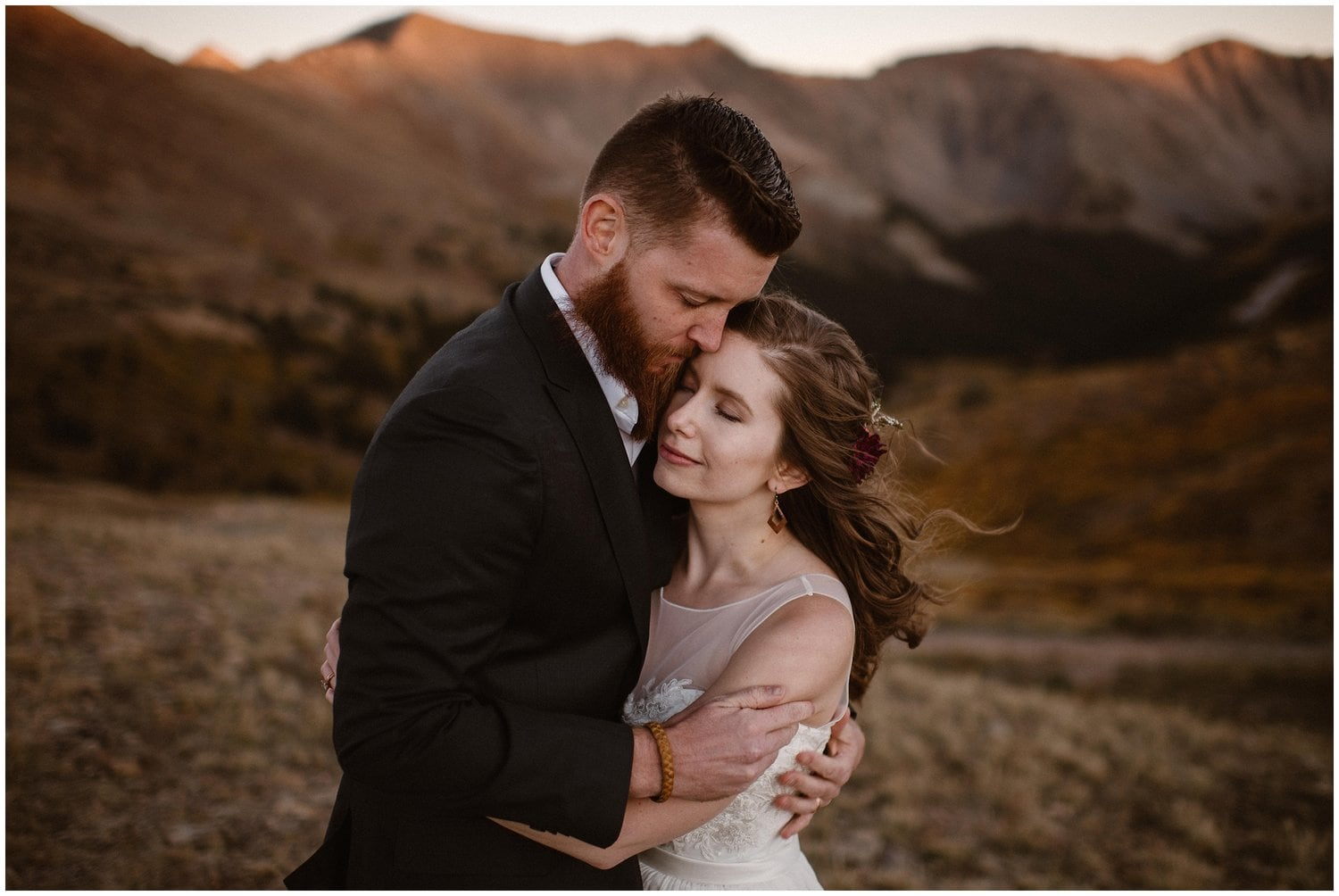 A bride and groom embrace in the mountains on their wedding day.