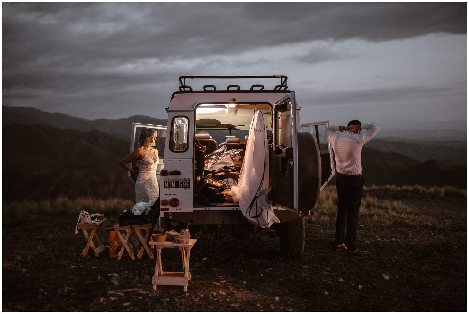 A bride and groom get ready on either side of a camper van in the early morning.