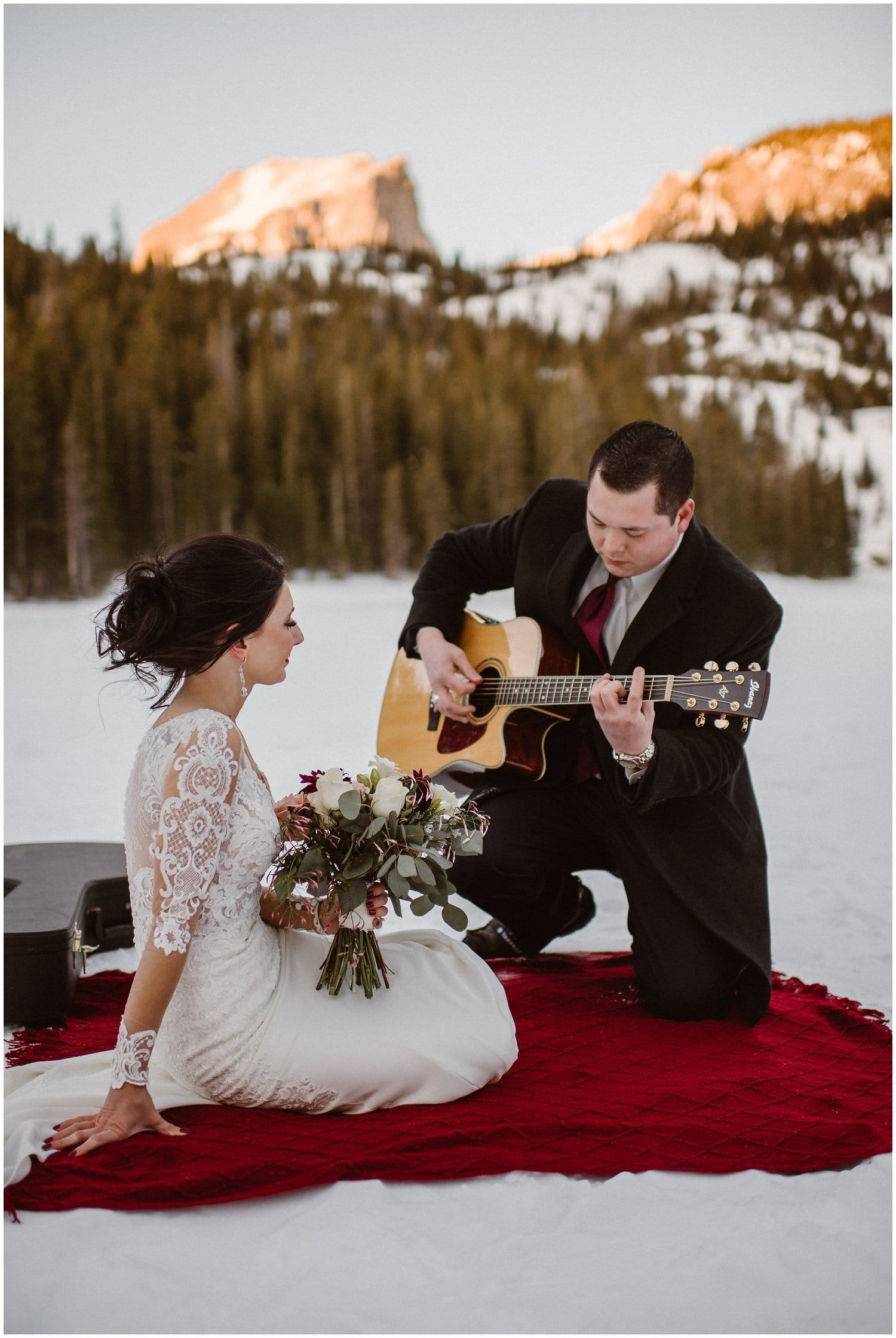Groom plays guitar for his bride in the snow while on a red blanket.