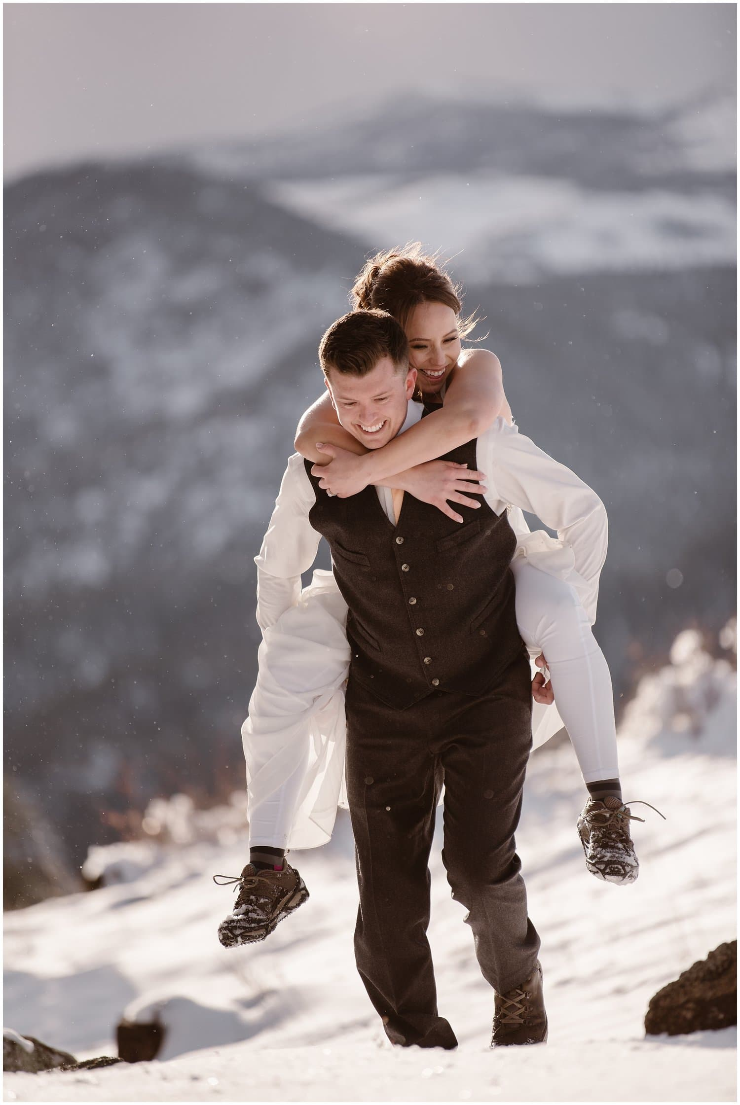 Groom carries bride on his back in the mountains on their wedding day.