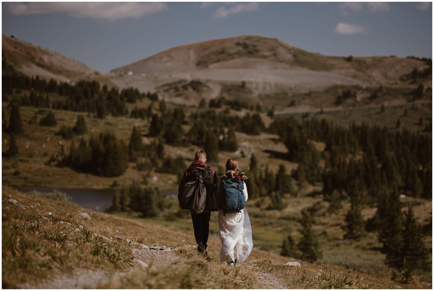 Bride and groom wear backpacks while hiking on their wedding day.
