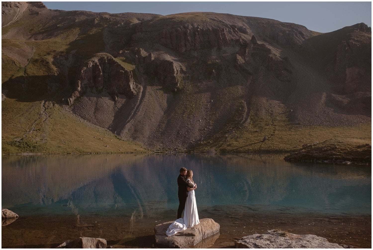 A couple stand on a rock in front a lake on their wedding day.