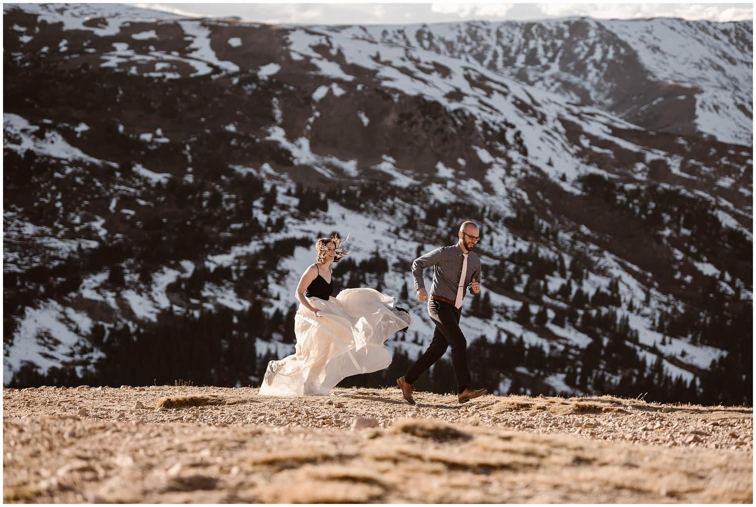 Bride and groom run in the mountains on their wedding day.