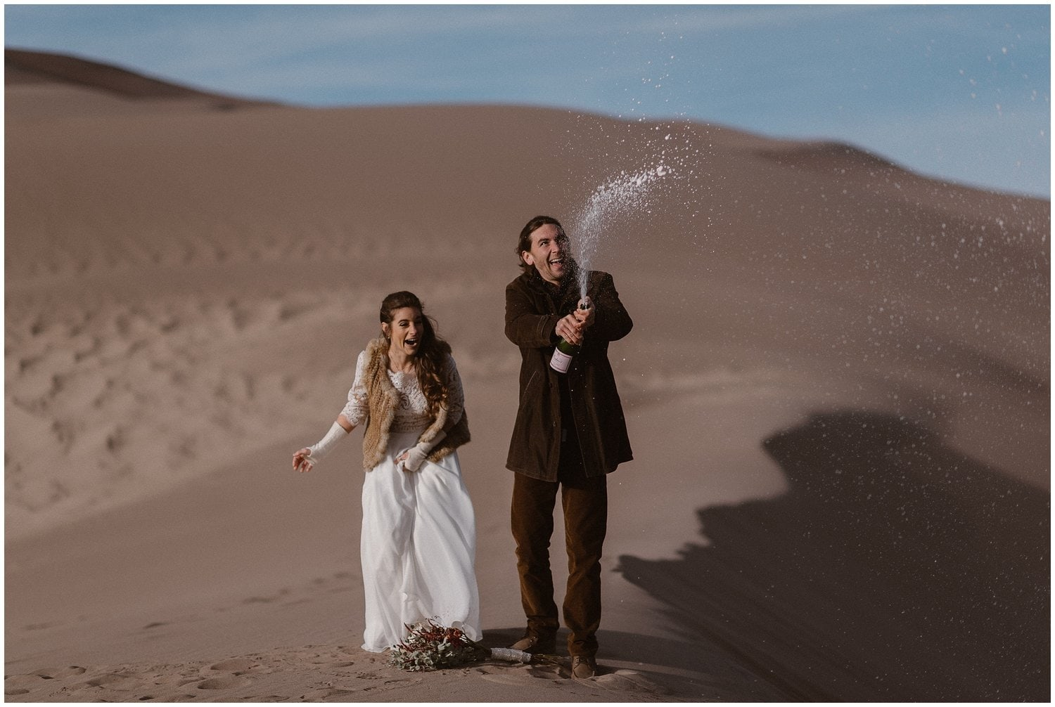 Bride and groom pop a bottle of champagne on the sand dunes on their wedding day.