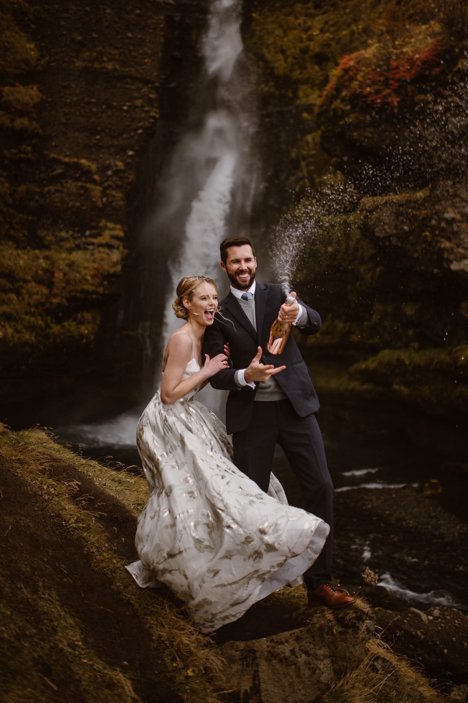 Bride and groom pop champagne on their wedding day in front of a waterfall.