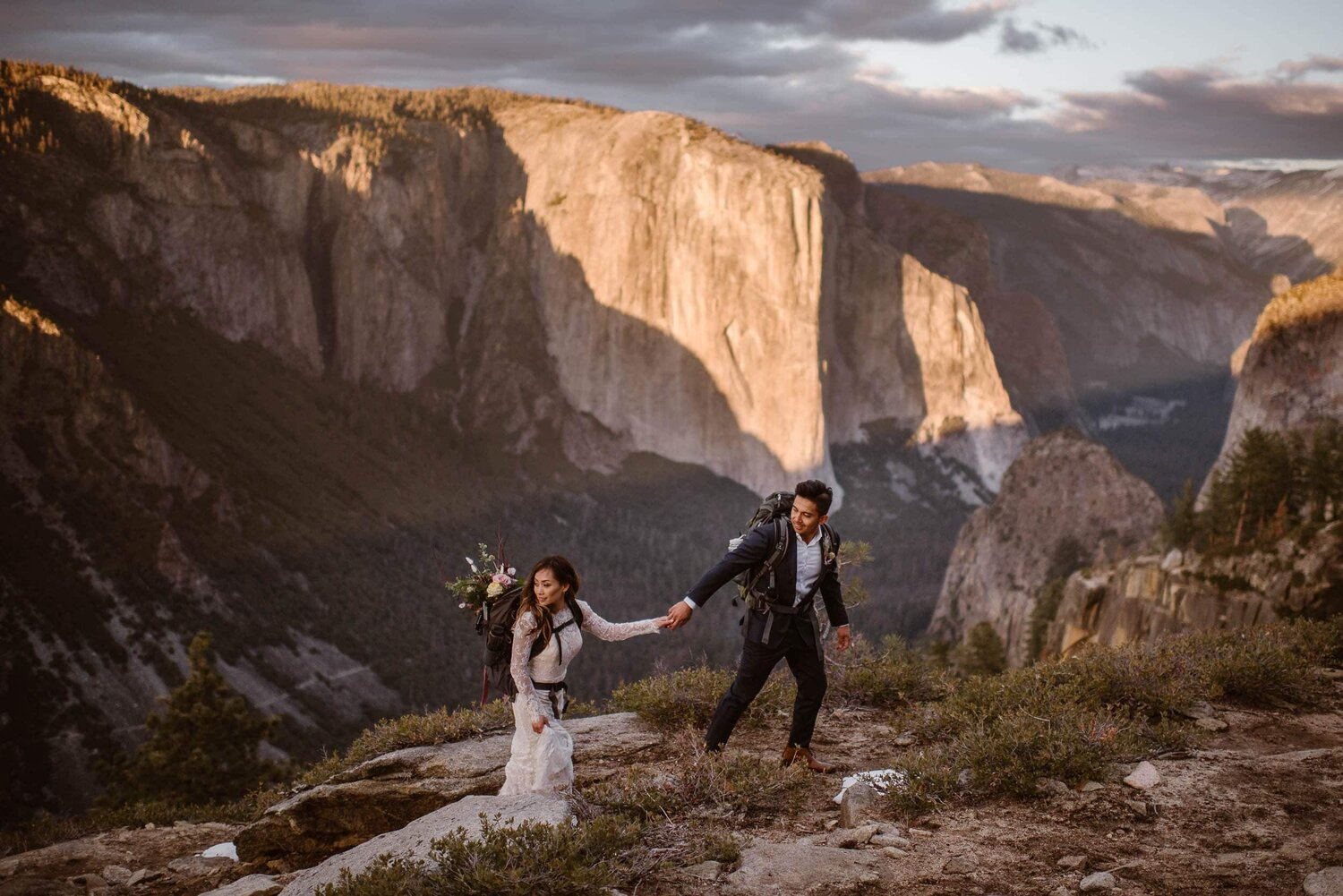 Bride and groom walk hand in hand while wearing backpacks in Yosemite National Park on their wedding day.