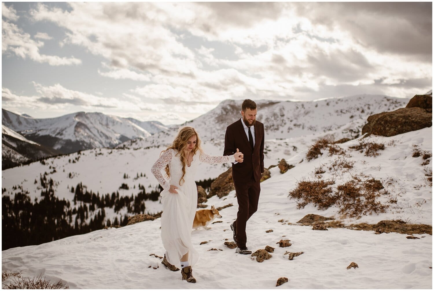 Bride and groom walk up the mountains in the snow on their wedding day.